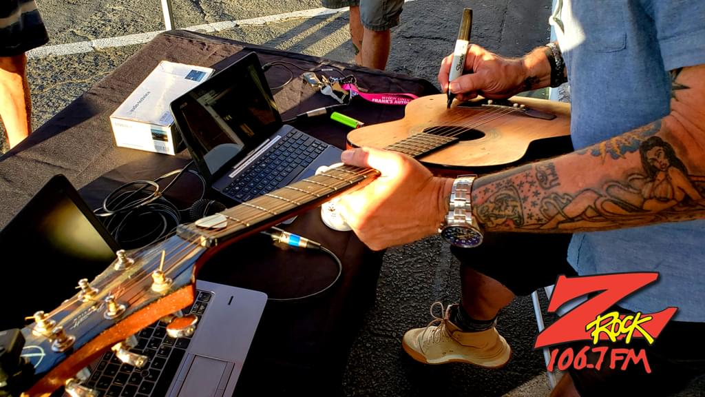 Tim Buc Moore signs a guitar during Wake the Buc Up at Betty Cakes & Coffee with 106.7 Z-Rock