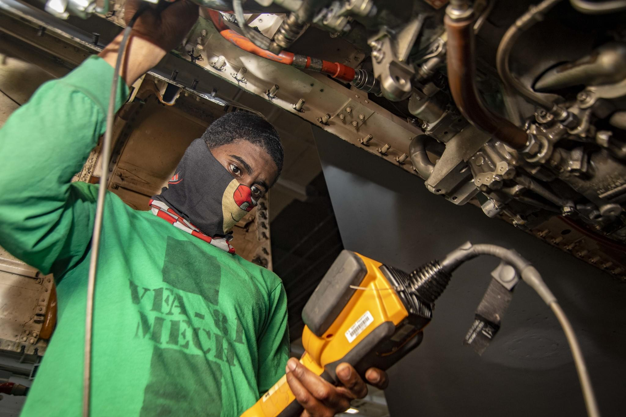 Military Spotlight: Newport News Sailor Inspects Engine on Aircraft Aboard U.S. Navy Warship