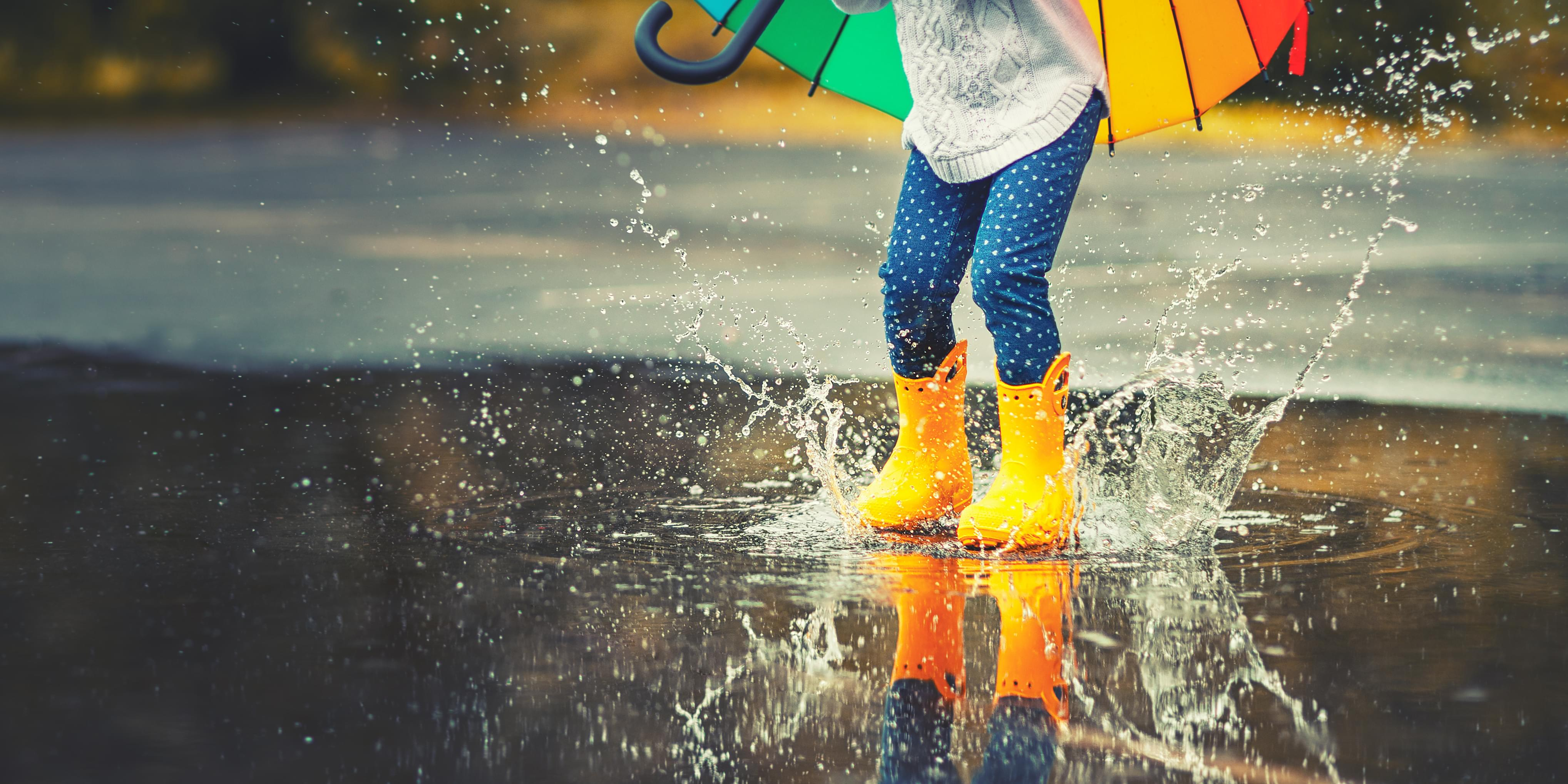 Feet,Of,Child,In,Yellow,Rubber,Boots,Jumping,Over,A
