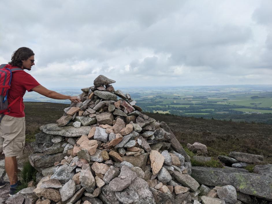 62. Adding a rock to the cairn on Mount Bennachie, Aberdeenshire, Scotland