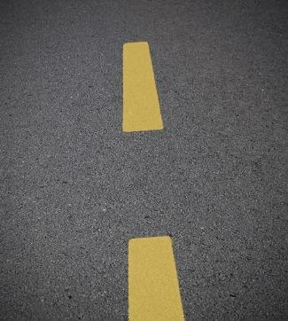 Yellow highway stripes on asphalt surface