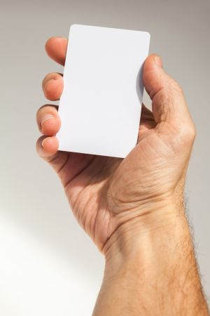 Male hand holds white empty card over gray wall background, close up photo with selective focus