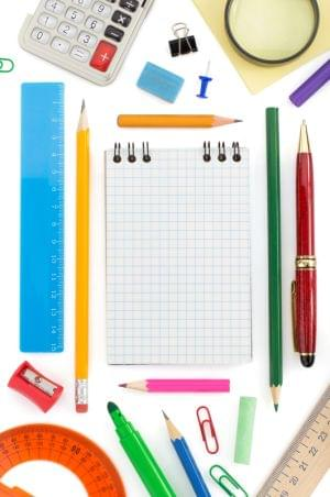 school supplies including pencils, a notebook, and a calculator isolated on white background