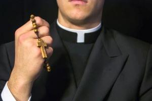 Young Priest Holding Rosary Beads