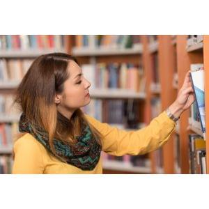 Happy Female Student With Book In Library