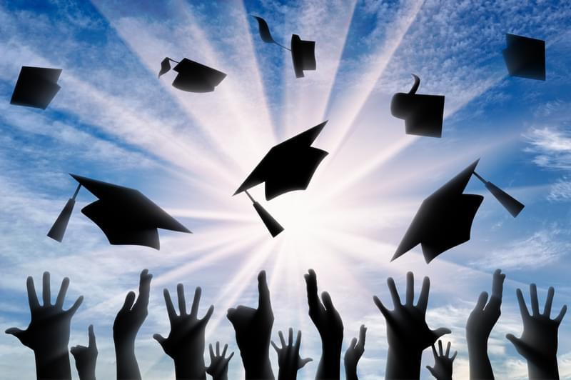 Hands throwing graduate cap in sky