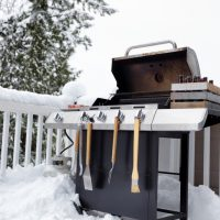 Barbecue cooker with bottled beer and beef meat ready for use in