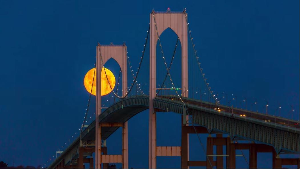 Stunning Snow Moon Changes from Orange to Pink Over Rhode Island's Newport Bridge