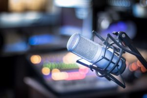 Microphone in a professional recording or radio studio, equipment in the blurry background