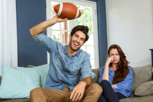 Couple watching american football match on television