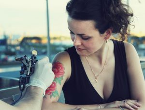 tattooer showing process of making a tattoo on young lwoman