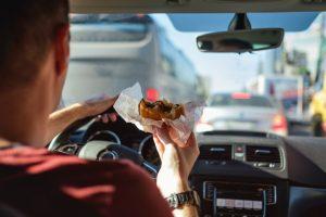 Man driving car while eating hamburger.