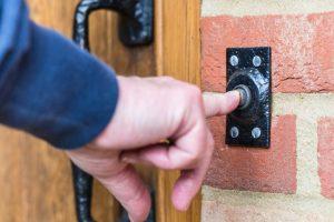 Closeup on a hand pressing a door bell button