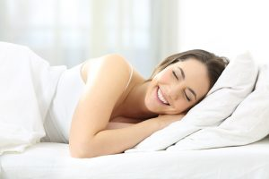 Happy woman sleeping comfortable in a bed