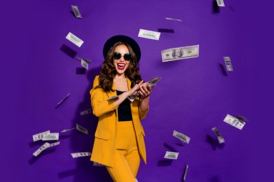 Portrait of her she nice attractive cheerful cheery positive trendy luxury wavy-haired lady throwing 100 hundred million expenses isolated over bright vivid shine violet lilac background