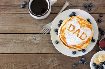 Fathers Day pancake breakfast with heart shape and DAD letters, above view corner border on rustic wood