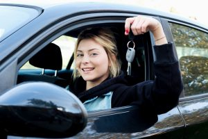 Young girl happy holding car key seated in her new car