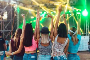 Back view of girls having fun at music festival