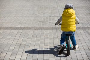 Back view on cute toddler boy riding his bike. Child on bicycle in the park.