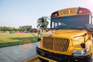 Yellow school bus parked next to playground