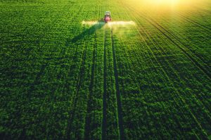 Aerial view of farming tractor plowing and spraying on big green field.