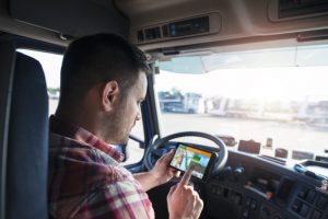 Truck driver using GPS to deliver goods. Transportation services with global positioning system.