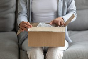 Close up view on woman lap is small carton box