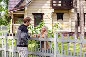 Middle aged man meeting smiling female neighbor in countryside and talking cheerfully to her over fence
