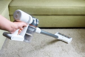 Wireless vacuum cleaner used on carpet in room. Housework with new white hoover. Person holds modern vacuum cleaner by sofa.