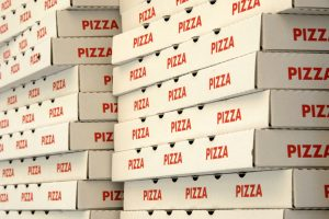 Two stacks of red and white pizza boxes