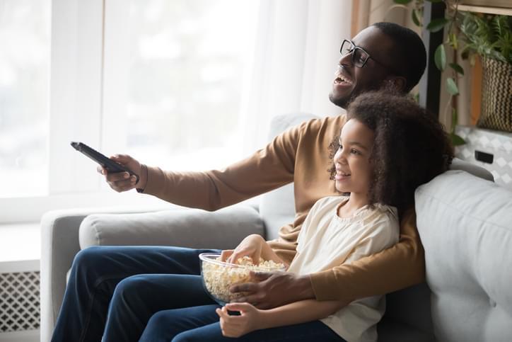 Happy black dad and daughter cuddle watching TV
