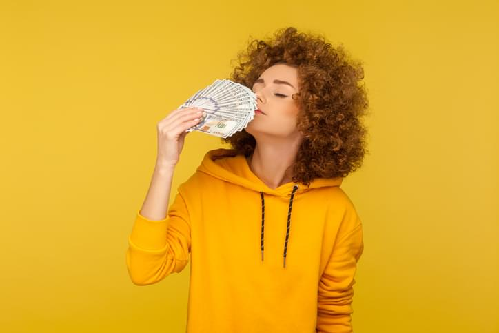Greed for money. Portrait of avaricious curly-haired woman in urban style hoodie smelling dollar banknotes