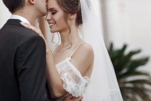 Happy couple in love, bride and groom cuddle and look at each other