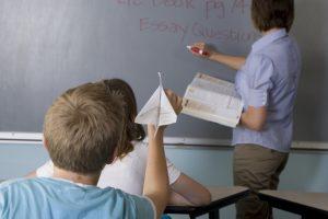 Student aiming paper plane at teacher writing on blackboard