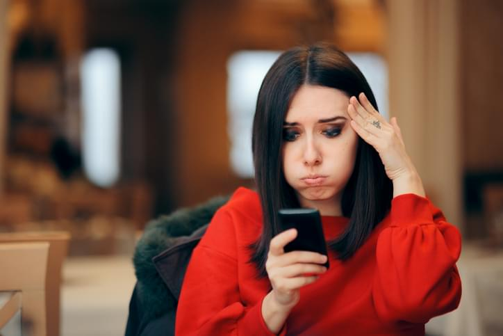 Stressed Woman Reading Text Message on Smartphone