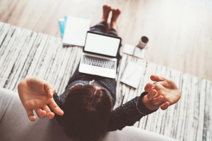 Businesswoman dressed in pajamas stretching her body after productively laptop working with morning coffee on floor office with laptop, papers top view shot. Distance work in quarantine time concept.