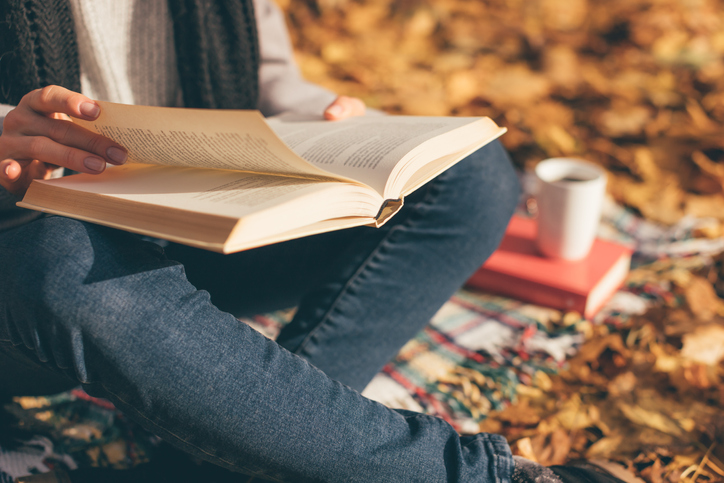 Cropped image of young woman sitting on blanket, reading book and drinking coffee or tea in autumn garden