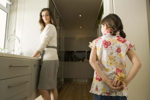 Girl in kitchen hiding cookies from mother