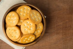 Round salted cracker cookies in wooden bowl putting on linen and wooden background