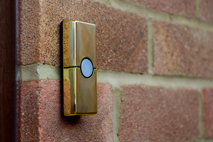 Brass-coloured doorbell on a brick wall