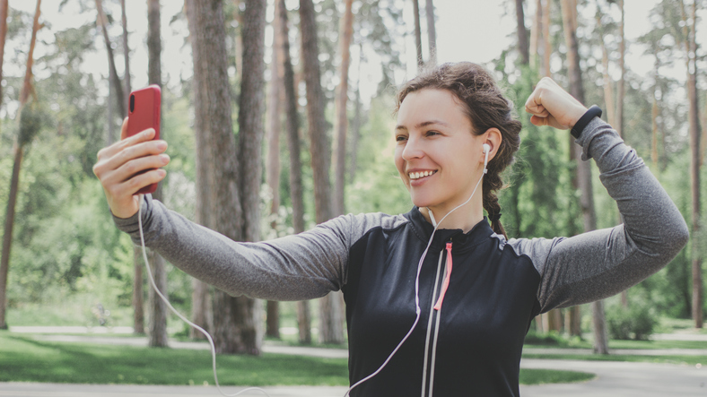 Young smiling caucasian fit athlete woman in headphones holding smartphone and showing biceps strong muscles,making video call,selfie,sharing social data after running,workout,training in park