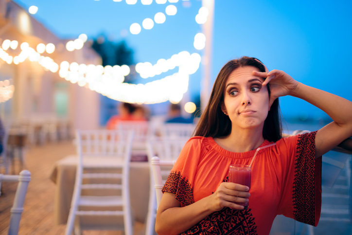Disappointed Bored Woman Holding a Cocktail at a Date