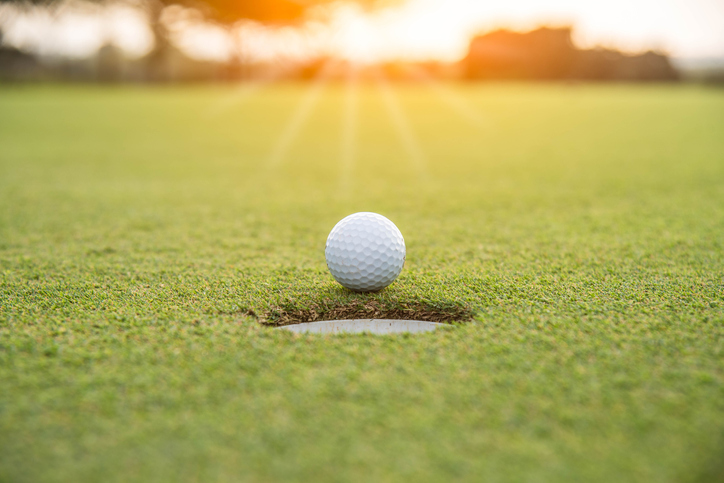 Golfer is putting golf ball on green grass at golf course for game with blur background and sunlight ray