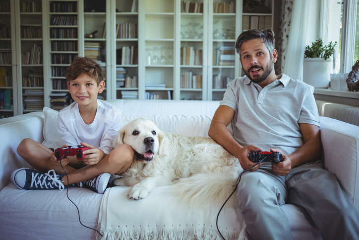 Father and son sitting on sofa with pet dog and playing video games