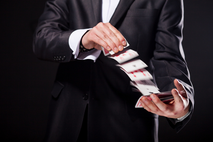 Young magician showing tricks using cards from deck. Close up.