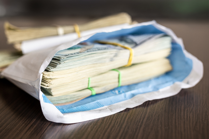Bundle of american dollar banknotes in white envelope on wooden table. Secondary black economy concept. Envelope wages. Bribery and economical crime
