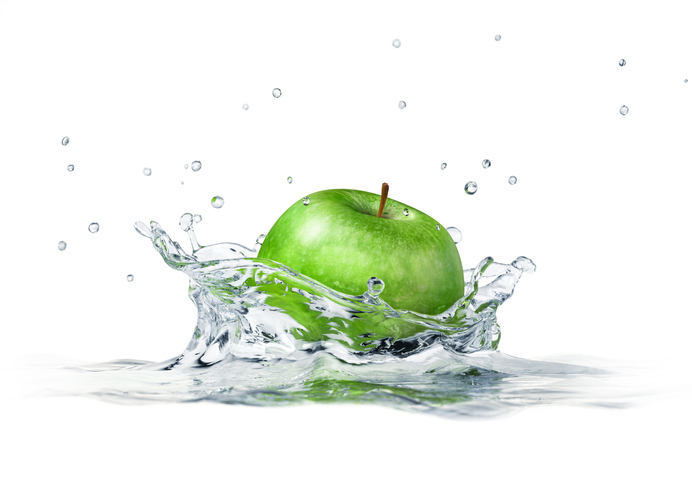 Green apple splashing into water. Close-up side view.