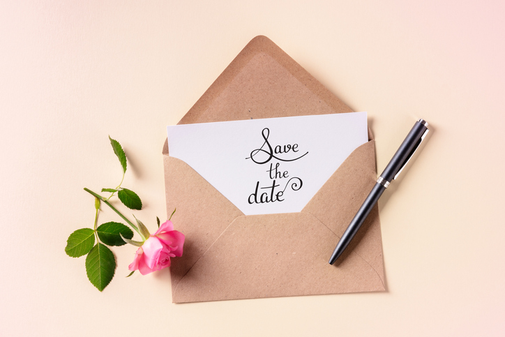 Save the date lettering on an invitation in a brown kraft envelope, shot from above on a pink pastel background