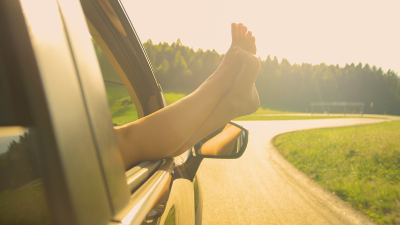 LENS FLARE: Unrecognizable girl drives with her feet through the car window.