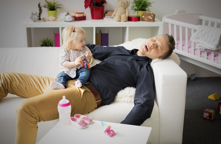 Tired father sleeping with baby on his lap.